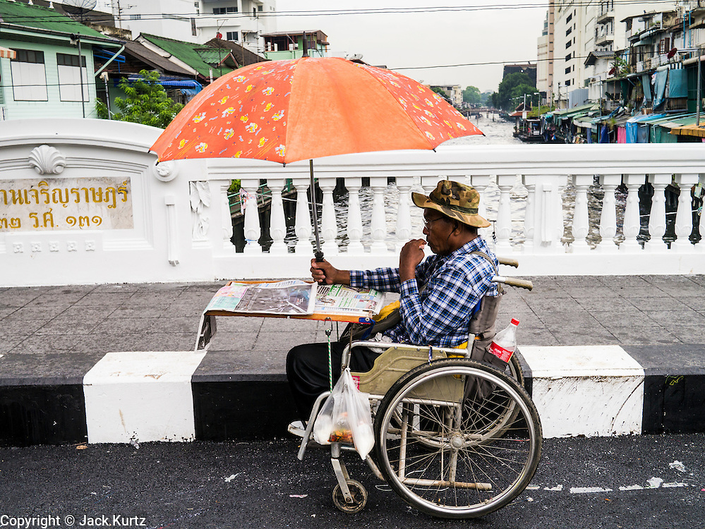 30 MAY 2013 - BANGKOK, THAILAND:   A man in a wheelchair sells lottery tickets on Krung Kasem Rd over Khlong Saen Saeb in Bobae Market in Bangkok. Bobae Market is a 30 year old famous for fashion wholesale and is now very popular with exporters from around the world. Bobae Tower is next to the market and  advertises itself as having 1,300 stalls under one roof and claims to be the largest garment wholesale center in Thailand.   PHOTO BY JACK KURTZ