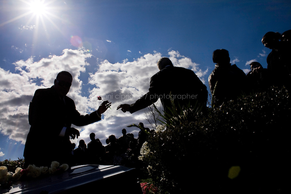 Harlem, New York, USA - April 14. Funeral home director Isaiah Owens grabs a rose that is passed to him by his assistant and that he will place on the casket before the burial on April 14, 2008 in Harlem, New York, USA.