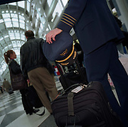 Waiting in line for a departing flight, an airline captain patiently queues with his flight baggage along with passengers. Rather than being on duty and flying the aircraft himself, he is travelling home as a passenger. On many commercial flights, off-duty air crew position as passengers. Airlines plan complicated logistics with cabin and cockpit crew members' duty rosters. This man's four stripes denotes his seniority as a captain who flies right-hand seat, in command of a airliner. In the US, pilots might also have National Guard careers flying jet fighters in times of conflict while off-duty in airline shifts. Picture from the 'Plane Pictures' project, a celebration of aviation aesthetics and flying culture, 100 years after the Wright brothers first 12 seconds/120 feet powered flight at Kitty Hawk,1903.