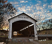 """Mecca Covered Bridge (150 feet long) was built in Burr Arch style over Big Raccoon Creek in 1873 by J.J. Daniels in historic Parke County, Indiana, USA. Golden sunset light beckons at the far opening. Puffy white clouds decorate the blue sky. The traditional """"Cross this bridge at a walk"""" sign required slow vehicle speed, but traffic is now diverted to an adjacent modern bridge. Panorama stitched from 2 photos."""