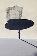 shadow of empty birdcage on a little round table