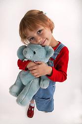 Young girl cuddling teddy bear,