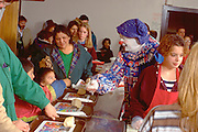 Clown serving Christmas dinner at church soup kitchen.  Minneapolis Minnesota USA
