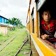 Member of Myanmar's Train Police lookin at moving train