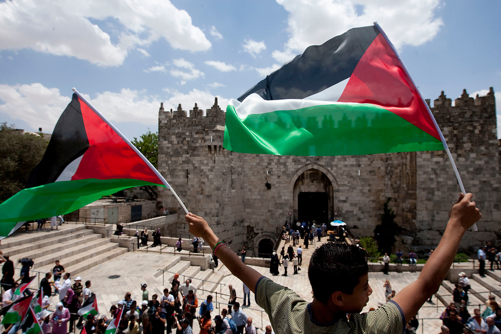 Palestinians wave their national flag outside Damascus Gate near Jerusalem's old city, during a protest against Jerusalem Day on May 21, 2009. Jerusalem Day marks Israel's capture of east Jerusalem and the re-unification of the city, which had been divided into Israeli and Jordanian sectors from Israel's establishment in 1948 until the 1967 war.