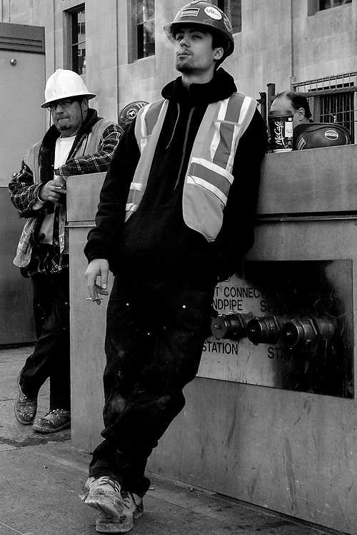 Construction has been ongoing at Union Station in Toronto for the past 7 or 8 years, and this results in many construction workers taking breaks during the morning rush or at any time during the day. I managed to take a photograph from the hip of these two workers taking a break. It was a challenging photograph to take as I was looking at my phone and randomly making images without composing. Fortunately, I was able to get one keeper photograph. The older fellow looked like he suspected I was making images, yet the younger man in the foreground had a really great confident look of confidence that really made the photograph.