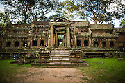 """01 JULY 2013 - ANGKOR WAT, SIEM REAP, SIEM REAP, CAMBODIA:  The east gate entrance to Angkor Wat. Angkor Wat is the largest temple complex in the world. The temple was built by the Khmer King Suryavarman II in the early 12th century in Yasodharapura (present-day Angkor), the capital of the Khmer Empire, as his state temple and eventual mausoleum. Angkor Wat was dedicated to Vishnu. It is the best-preserved temple at the site, and has remained a religious centre since its foundation– first Hindu, then Buddhist. The temple is at the top of the high classical style of Khmer architecture. It is a symbol of Cambodia, appearing on the national flag, and it is the country's prime attraction for visitors. The temple is admired for the architecture, the extensive bas-reliefs, and for the numerous devatas adorning its walls. The modern name, Angkor Wat, means """"Temple City"""" or """"City of Temples"""" in Khmer; Angkor, meaning """"city"""" or """"capital city"""", is a vernacular form of the word nokor, which comes from the Sanskrit word nagara. Wat is the Khmer word for """"temple grounds"""", derived from the Pali word """"vatta."""" Prior to this time the temple was known as Preah Pisnulok, after the posthumous title of its founder. It is also the name of complex of temples, which includes Bayon and Preah Khan, in the vicinity. It is by far the most visited tourist attraction in Cambodia. More than half of all tourists to Cambodia visit Angkor.      PHOTO BY JACK KURTZ"""