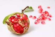 Open Pomegranate with seeds on white background