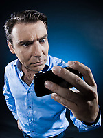 caucasian man looking at phone anger portrait isolated studio on black background