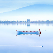Boat on a calm lake, blue tones.