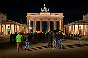 Tourists visit the Brandenburg Gate at night on 11th October 2019 in Berlin Germany. The 18th century Neoclassical monument is built in the Western part of Berlin and is one of the most famous landmarks in Germany. Throughout its existence, the Brandenburg Gate is often a site for major historical events and is considered not only as a symbol of the tumultuous history of Europe and Germany, but also of European unity and peace.