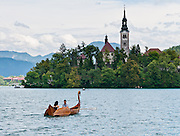 A rowboat with swan prow head approaches the medieval church on glacially formed Lake Bled (Slovene: Blejsko jezero) in the Julian Alps in northwestern Slovenia, Europe. The lake surrounds Bled Island (Blejski otok, the only natural island in Slovenia), upon which stands the Pilgrimage Church of the Assumption of Mary (Slovenian: Cerkev Marijinega vnebovzetja), built in the 15th century and now popular for romantic weddings. Lake Bled hosted the World Rowing Championships in 1966, 1979, 1989, and 2011. The lake is 35 kilometers from Ljubljana International Airport.