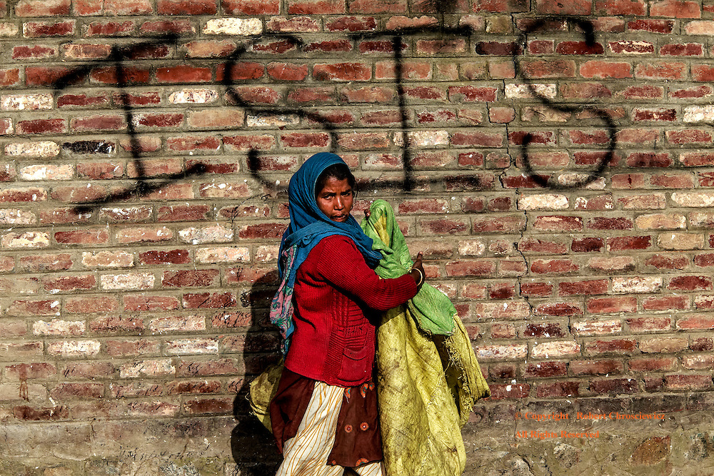 """The Face of ISIS?: A woman carries on with her duties passing in front of a brick wall that is tagged with """"ISIS"""", Srinagar India.<br /> <br /> This begs the question: is ISIS born of an extreme doctrine or rather is it fundamentally a projection of the will of the people?"""