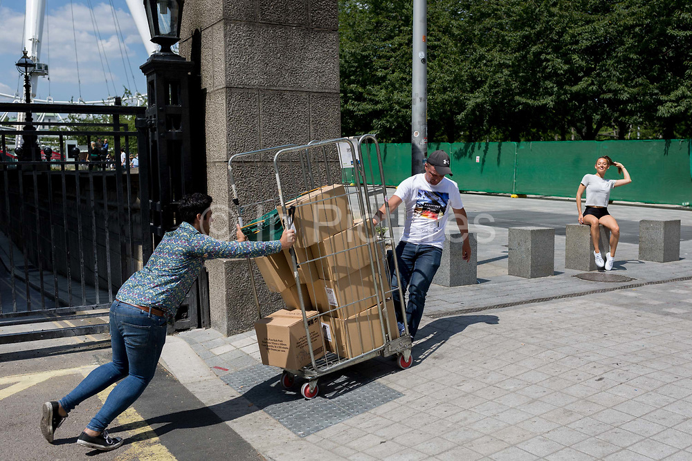 As a young woman poses for photos on the Southbank, deliverymen push a cage of unstable, then toppling boxes, on 16th July 2019, in London, England. Part of a larger sequence of 10 images.