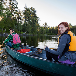 A young couple paddles a canoe on Long Pond in Maine's north woods. At the Appalachian Mountain Club's Gorman Chairback Lodge. Near Greenville, Maine.