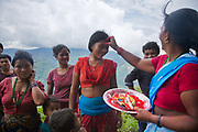 Sanamaya Chepang is giving Tika to people at the gathering, a Hindu tradition meaning good luck and health. The Chepangs is an ethnic group which used to be nomadic. Only recently have the settled and their settlements are high up in the mountains.
