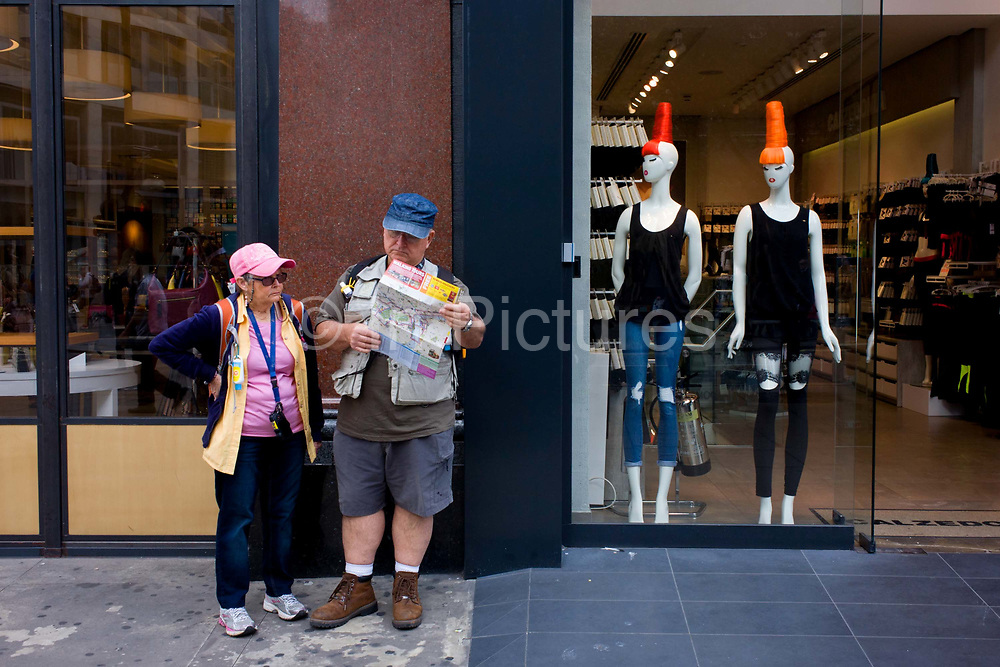 Two tourists in peak caps and two mannequins in matching headwear. In an odd moment on central London's Oxford Street, UK, the man and woman look out of place in an otherwise stylish street selling clothing and fashion. Wearing tourist attire - hiking boots and shorts, the man looks at the map of the city while his partner of wife stands with hands on hips waiting for instructions and directions to reach whatever area of London they want to reach. The models on the left have eccentric hair, piles of colour with skinny leggings that also contradict the look of the tourists.