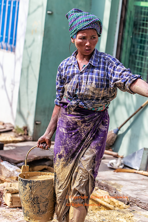 Hard Days Work: A woman putting in a hard day's work, carrying buckets of a seemingly endless supply of muddy excrement, from a work site in Mandalay Myanmar.