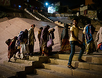 Varanasi, INDIA - CIRCA NOVEMBER 2018: People at night walking on the ghats of Varanasi. Varanasi is the spiritual capital of India, the holiest of the seven sacred cities and with that many rituals and offerings are performed daily by priests and hindus.
