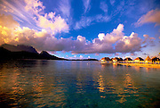 Big puffy clouds sit above blue ocean waters where a line of vacation huts sit in Tahiti