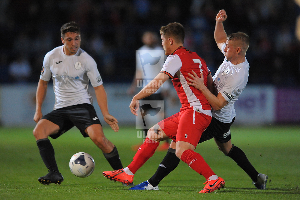 TELFORD COPYRIGHT MIKE SHERIDAN Adam Walker and Darryl Knights battle with Harriers Declan Weeks during the National League North fixture between AFC Telford United and Kidderminster Harriers on Tuesday, August 6, 2019.<br /> <br /> Picture credit: Mike Sheridan<br /> <br /> MS201920-006