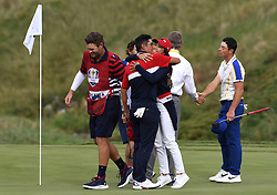 Team USA's Collin Morikawa (left) hugs wife Katherine Zhu after securing enough points to win the Ryder Cup for Team USA on the 18th hole as Team Europe's Viktor Hovland (right) looks dejected during day three of the 43rd Ryder Cup at Whistling Straits, Wisconsin. Picture date: Sunday September 26, 2021.