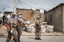 JOHANNESBURG, April 1, 2020  Policemen and a soldier patrol on a street in Johannesburg, South Africa, March 31, 2020. South African President Cyril Ramaphosa on Monday defended the 21-day national lockdown against the coronavirus pandemic which began on midnight Thursday, saying it is ''absolutely necessary.'' (Photo by Yeshiel PanchiaXinhua) (Credit Image: © Xinhua via ZUMA Wire)