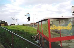 Boy jumping off bus shelter; Bradford council estate; UK