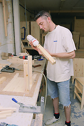 Cabinet maker using glue to construct carcass of bedside cabinet,