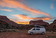 An orange sunset illuminates clouds in the blue sky at dusk over our 1999 Volkswagon Eurovan Camper. We camped on BLM land on Blue Notch Canyon Road, a mile west of Highway 95 in White Canyon, near Hite Marina, Utah, USA.