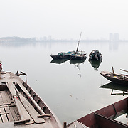 Wooden sampans on West Lake (Ho Tay) in Hanoi, Vietnam. The thick haze mostly obscures the far shore.