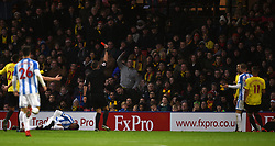 Watford's Troy Deeney (right, obscured) is shown a red card during the Premier League match at Vicarage Road, Watford.