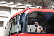 Woman wearing a face mask on the top deck of a bus as lockdown continues and people observe the stay at home message in the capital on 12th May 2020 in London, England, United Kingdom. Coronavirus or Covid-19 is a new respiratory illness that has not previously been seen in humans. While much or Europe has been placed into lockdown, the UK government has now announced a slight relaxation of the stringent rules as part of their long term strategy, and in particular social distancing.