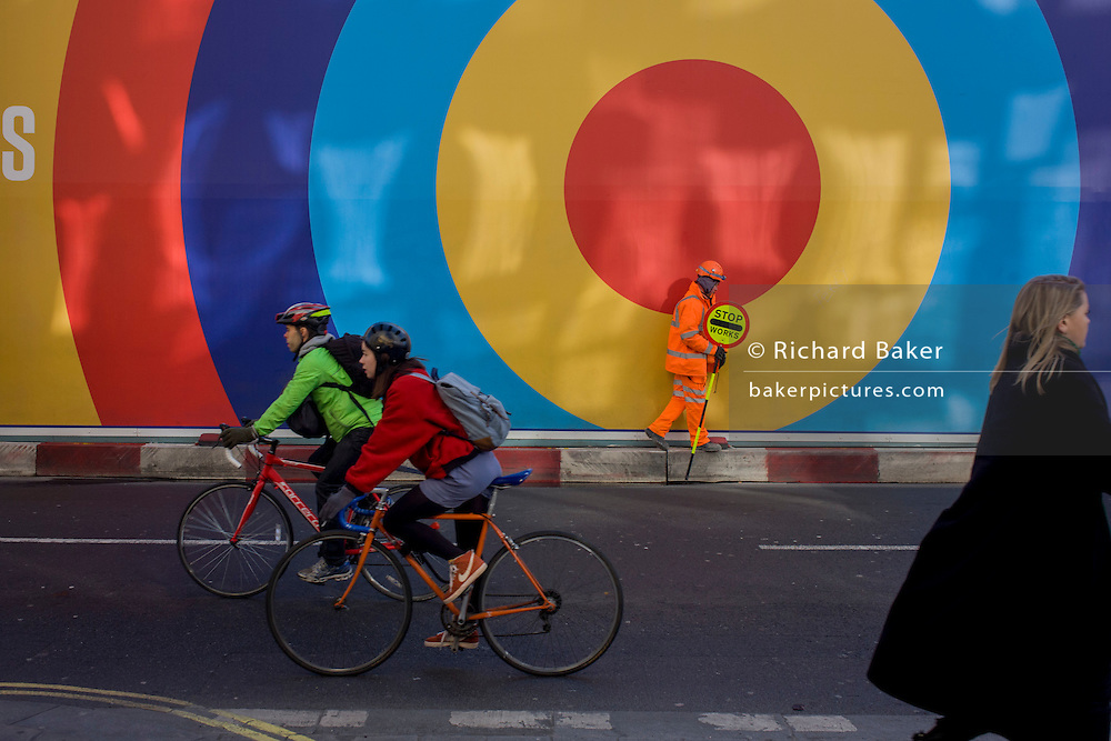 Cyclists pass a banksman working on a nearby building site, holds his Stop sign under the large circles of a construction hoarding on central London's Oxford Street.