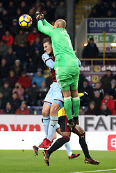 Watford goalkeeper Heurelho Gomes punches the ball clear under pressure from Burnley's Chris Wood during the Premier League match at Turf Moor, Burnley.