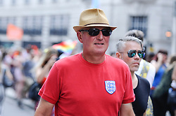 © Licensed to London News Pictures. 07/07/2018. LONDON, UK. An England fan in the capital to watch the England v Sweden World Cup football match views the annual Pride in London Parade, the largest celebration of the LGBT+ community in the UK.  Photo credit: Stephen Chung/LNP