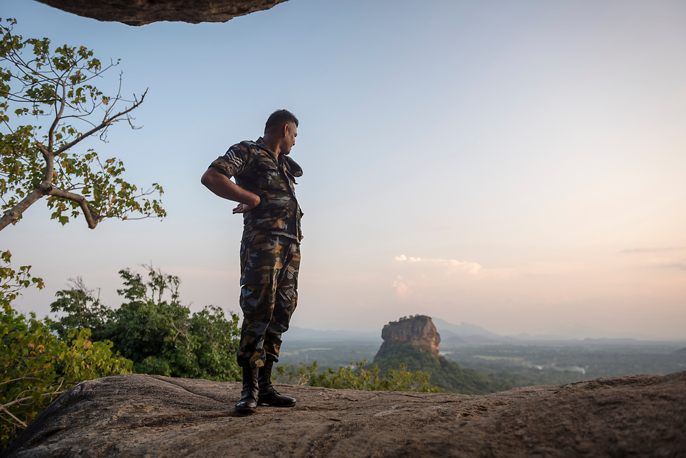 A member of the Sri Lankan air force looks toward the Sigiriya rock fortress. He's standing on Pidurangala Rock, a mountain peak best known for its excellent view of the famous rock fortress.