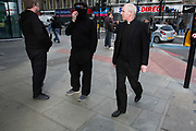 Anarchists gather as a black bloc for the Fuck Parade to party and protest at the class and wealth divide between rich and poor and the gentrification of London, the demonstration was organised by anarchist group Class War on May 1st 2016 in London, United Kingdom. The parade is now part of the May Day activism calendar as dissatisfaction about the establishment, the police and the inadequacy of the press is highlighted. A member of the clergy wearing a dog collar passes the first protesters to arrive.
