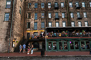 Savannah, Georgia, USA - July 29, 2021: People drink and dine in the historic heart of Savannah at the River Street Inn.