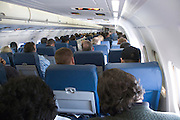 businessmen and other passengers in coach class while airplane is in flight