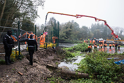 HS2 security guards and enforcement agents monitor two anti-HS2 activists wading in the river Colne at Denham Ford in order to try to delay bridge building works for the HS2 high-speed rail link on the first day of the second national coronavirus lockdown on 5 November 2020 in Denham, United Kingdom. Prime Minister Boris Johnson has advised that construction work may continue during the second lockdown but those working on construction projects are required to adhere to Site Operating Procedures including social distancing guidelines to help prevent the spread of COVID-19.