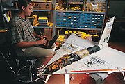 Aerospace engineer Scott Newbern programs the flight computer in the Gryphon, one of the prototypes in the fleet of small robot jets under development at AeroVironment, a company founded in 1971 by inventor Paul MacCready. AeroVironment  , Simi Valley, California. From the book Robo sapiens: Evolution of a New Species, page 156-157.