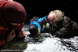(L>R) Sean Lichter, Frederic Billon and Bertrand Dubet on the frozen lake to make a Baikal Kiss (drill a hole in the ice and fill it with vodka to drink) during the wrap party after the Baikal Mile Ice Speed Festival. Maksimiha, Siberia, Russia. Saturday, February 29, 2020. Photography ©2020 Michael Lichter.