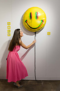 A woman views a gian smiley balloon artwork by Fanakapan at the preview of Moniker Art Fair on October 04, 2018, taking place during Frieze Week at the Old Truman Brewery in London, England. The art fair embraces contemporary urban art from emerging and established artists and this year, the shows theme is Uncensored, shedding light on social, economic and ecological issues.