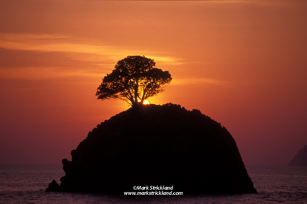 The sun sets behind one of many small limestone islets in Burma's Mergui Archipelago, High Rock.  High Rock, Mergui Archipelago, Burma/Myanmar, Andaman Sea