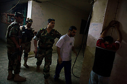 An Iraqi Army lieutenant leads away a suspect during a daytime raid in a darkened apartment building in central Adhamiya on Thursday April 27, 2007. The raid, which was led by Iraqi soldiers, netted three suspected IED triggermen.
