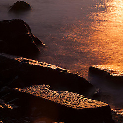 Sunrise reflections on the rocks at Great Island Common in New Castle, New Hampshire.