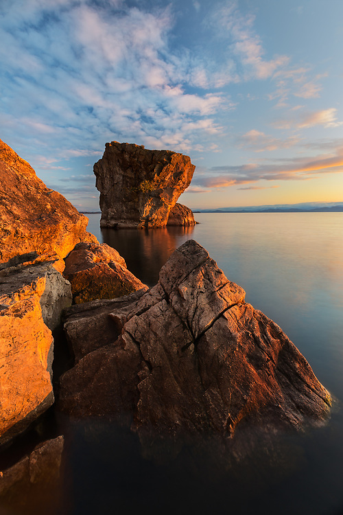 Warm light bathes the shoreline rocks on Lake Champlain, near Burlington, Vermont