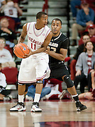Nov 16, 2011; Fayetteville, AR, USA;  Arkansas Razorbacks guard BJ Young (11) looks to make a pass under pressure from Oakland Grizzlies guard Reggie Hamilton (23) during a game at Bud Walton Arena. Arkansas defeated Oakland 91-68. Mandatory Credit: Beth Hall-US PRESSWIRE