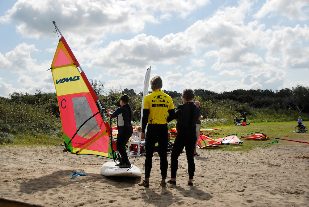 Vrouwenpolder, 11  aug, 2007. Vader en zoon op surfles. Instructeur geeft les hoe je op een zeilplank kan blijven staan. Surfschool aan het Veerse meer..Father and his son taking their first lessons how to surf. An instructor is theaching them how to stay on the board and to get the wind in the sail..Foto: (c) Renee Teunis